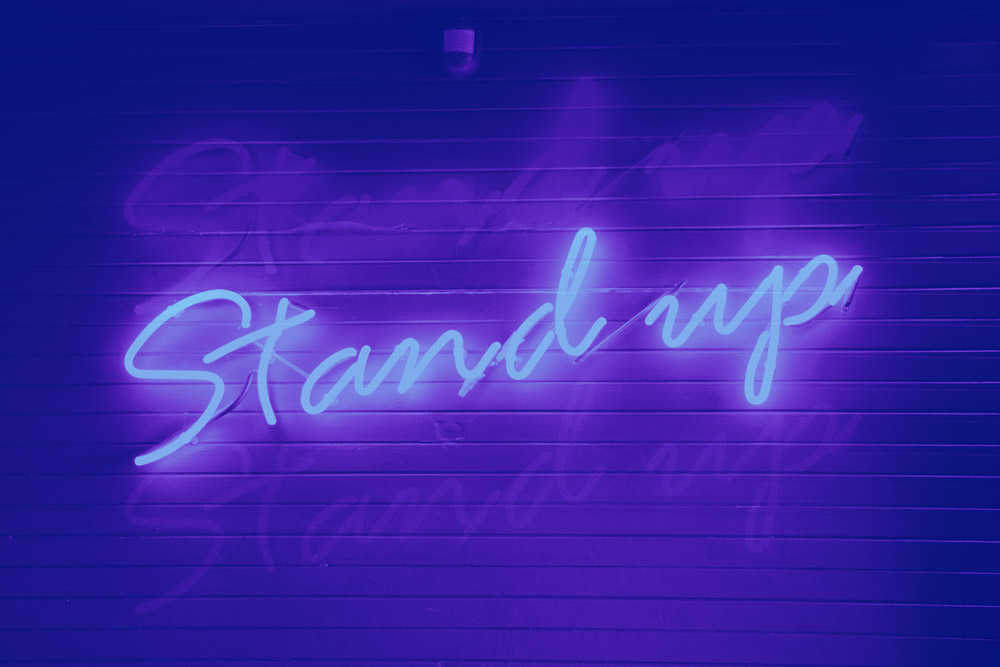 a neon sign on a wall that says stand up