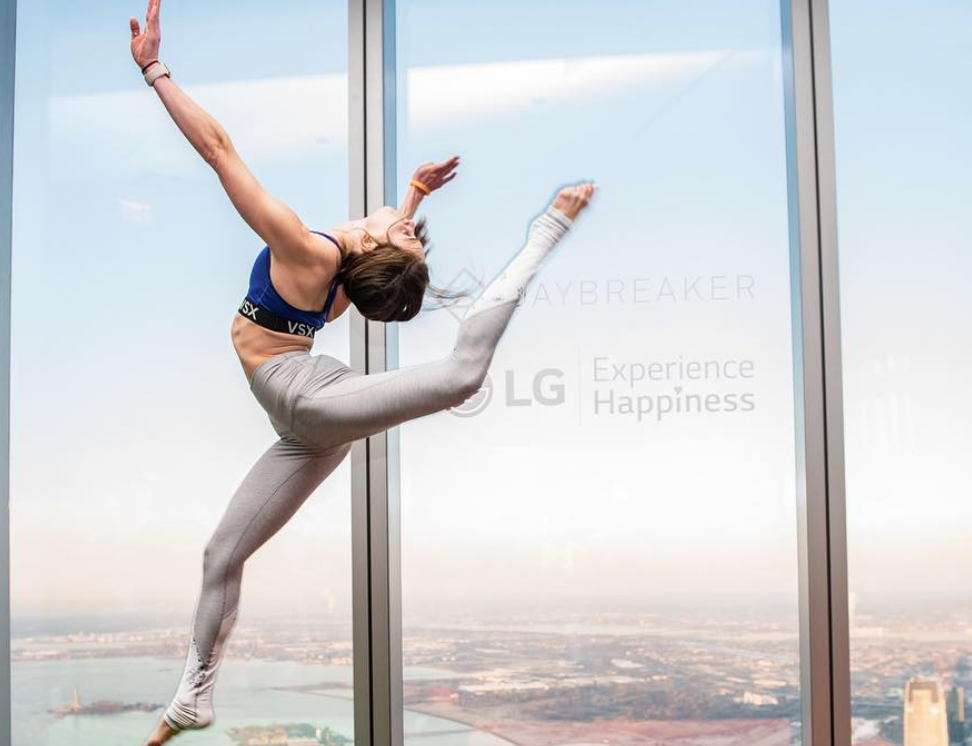 Image of a woman in workout gear doing a high kick dance move in front of a window for LG Experience Happiness