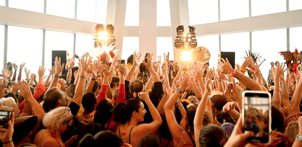 A photo of a crowd of people with their hands in the air at an LG Experience Happiness event