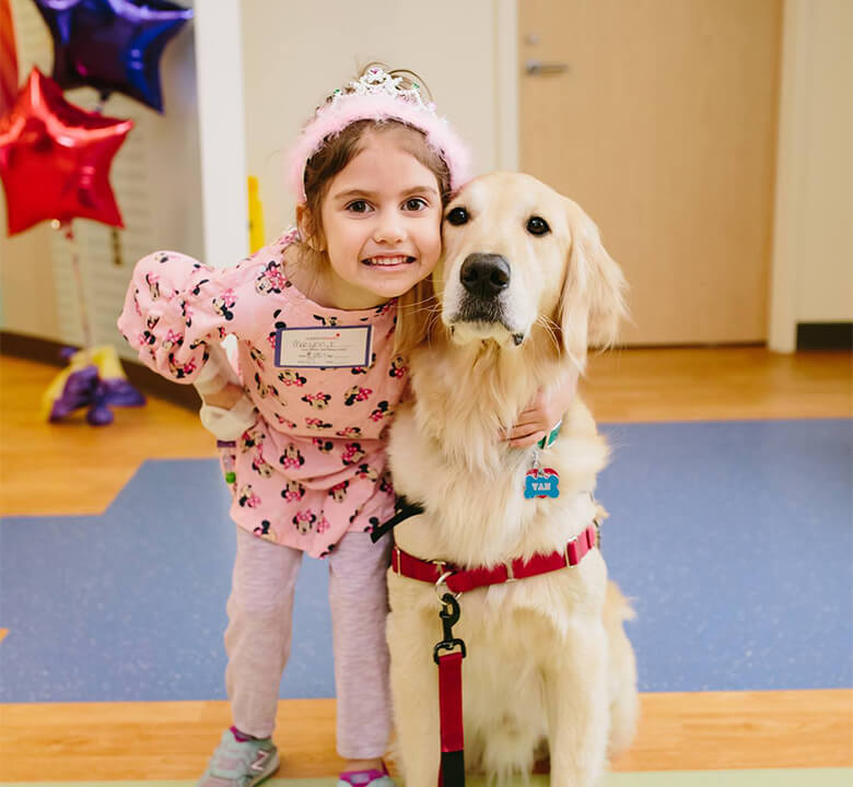 girl with dog posing for photo at childrens hospital