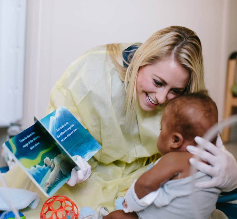 a nurse reading a book to a young child