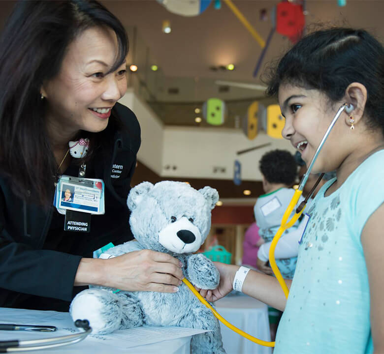 a nurse giving a young female patient a stuffed teddy bear