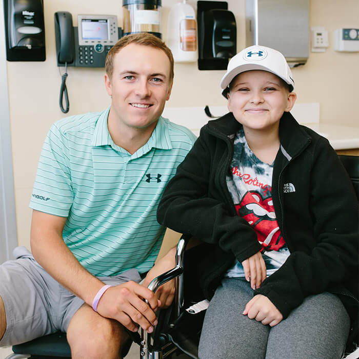 a man and his son smiling at the camera from a hospital room