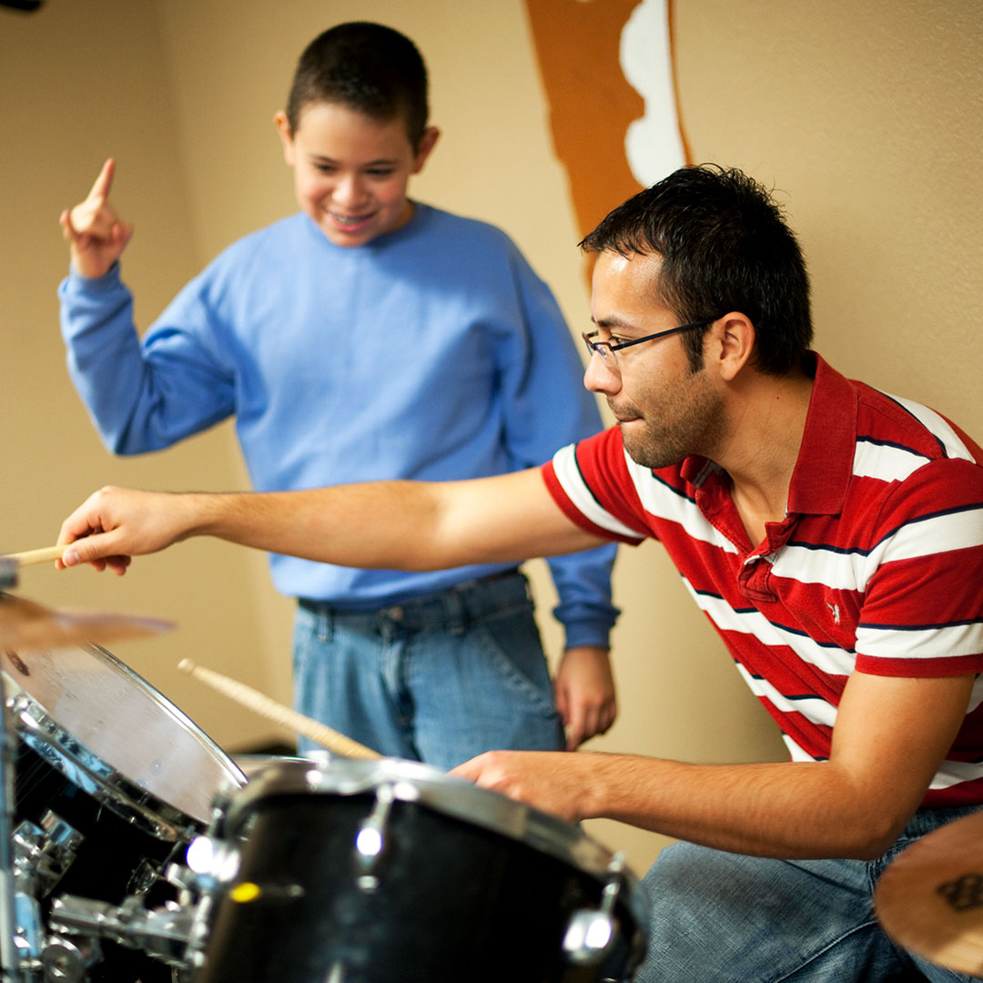Boy playing the drums with his dad