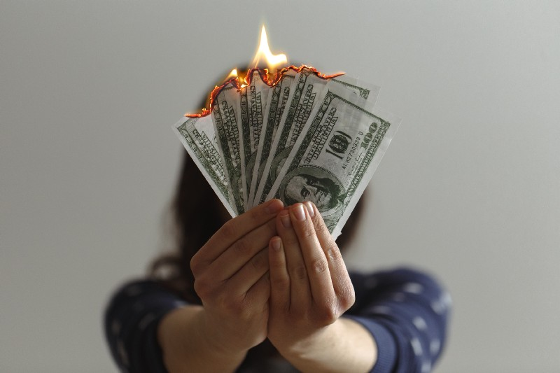 a woman holding burning money
