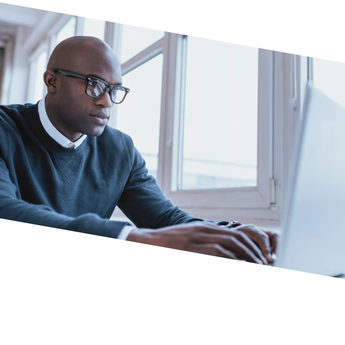 African American man with glasses typing on a laptop