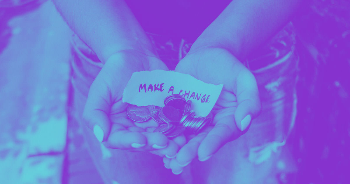"""cupped hands holding a pile of coins and a paper reading """"make a change"""""""